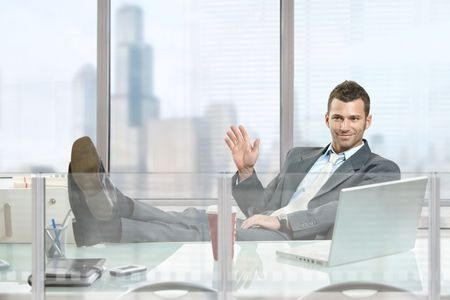Relaxed businessman  sitting at desk in front of office windows, waving hand and smiling. photo