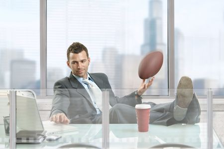 Relaxed businessman sitting at desk in front of office windows, holding football and smiling. Stock Photo - 5758642