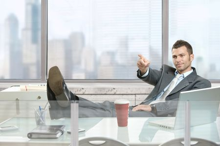 Relaxed businessman sitting at desk in front of office windows, pointing and looking at camera. photo
