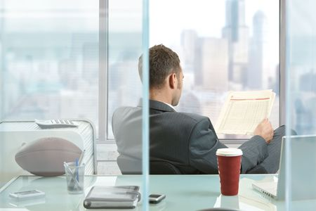 news room: Relaxed businessman  sitting at desk in front of office windows, reading nwespaper. Stock Photo