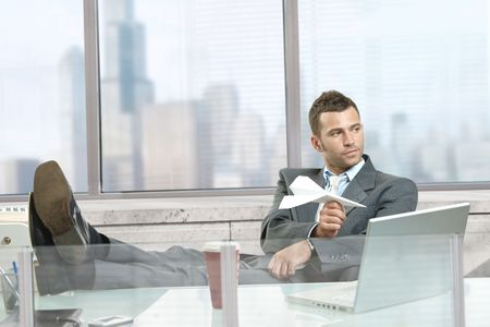 papierflugzeug: Relaxed Gesch�ftsmann sitzt am Schreibtisch vor dem B�ro-Fenster, das Spiel mit Papier Flugzeug, l�chelnd.