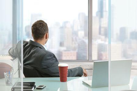 Relaxed homme d'affaires assis à son bureau dans le bureau, en regardant par les fenêtres de gratte-ciel du centre-ville.