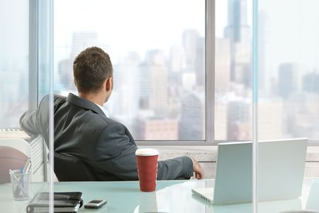 Relaxed businessman sitting at desk in office, looking out the windows to downtown skyscrapers. photo
