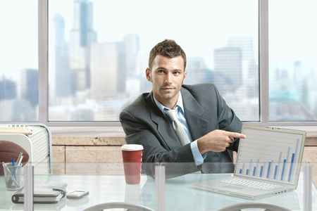 Businessman sitting at desk in office, pointing to charts on laptop computer screen. photo
