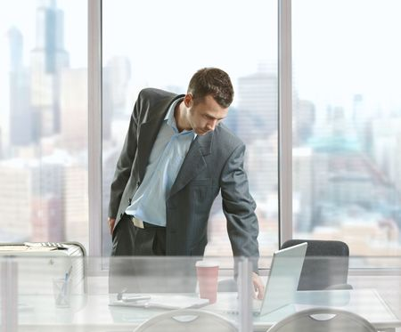 Businessman standing at desk in front of office windows, using laptop computer. Stock Photo - 5758671