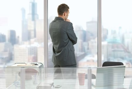 Businessman thinking in office, looking out of windows to downtown vista. Imagens