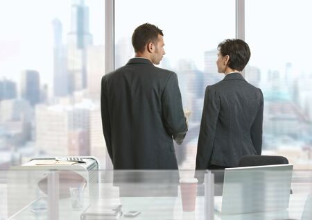 Two businesspeople standing at desk in office, looking out the windows and talking. photo