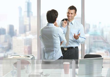 dos personas conversando: Dos de pie en el escritorio de los empresarios en el edificio de oficinas del centro, hablar y sonre�r. Foto de archivo