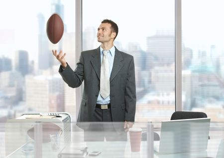 Relaxed businessman standing in front of office windows, playing with football and smiling. photo