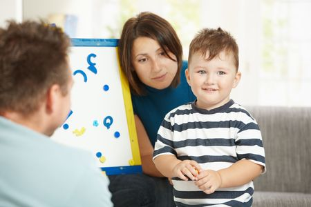 Father, mother and boy child playing together with toy whiteboard, letters and numbers. photo
