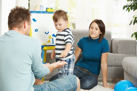 Father, mother and boy child playing together with toy whiteboard, learning letters and numbers. Stock Photo - 5766802