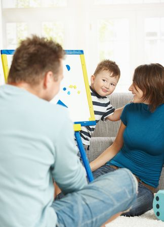 Father, mother and boy child playing together with toy whiteboard, learning letters and numbers. photo