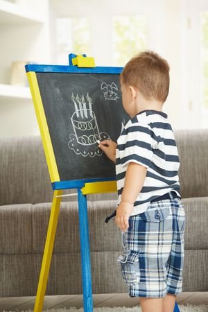 Little boy drawing birthday cake with chalk on blackboard at home. photo
