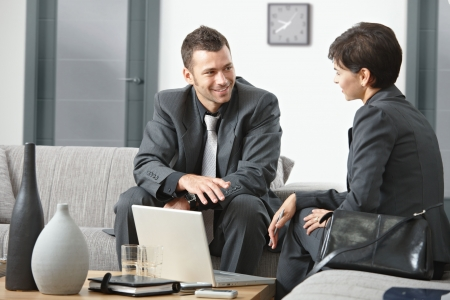 Young business people having meeting at office sitting on sofa talking. Stock Photo - 5767069