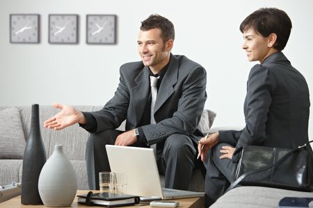 collaborating together: Young business people having meeting at office sitting on sofa talking to partner.