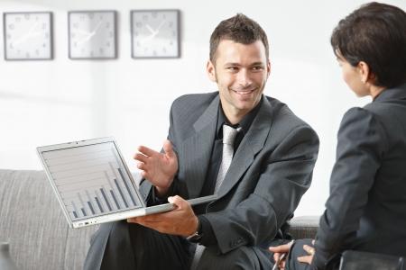Joven empresario gráfico que muestra financieros al socio en la oficina, sonriendo. Foto de archivo