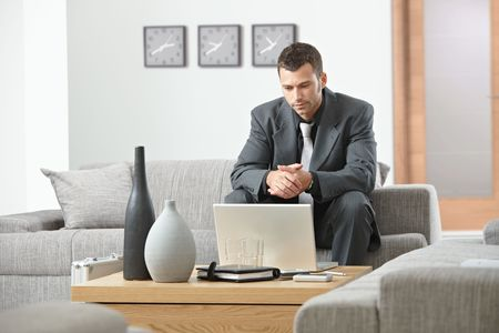 using computer: Young businessman sitting on sofa at office, working with laptop computer.