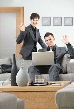 Young business people having meeting at office sitting on sofa greeting a partner, looking away. photo