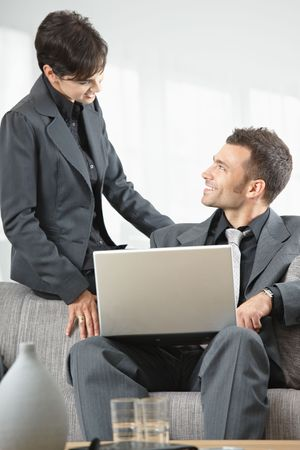 Young business people having meeting at office sitting on couch working on laptop computer. Stock Photo - 5766928