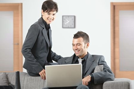 Young business people having meeting at office sitting on couch working on laptop computer. Stock Photo - 5766919
