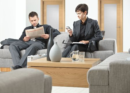 anteroom: Business people sitting on sofa at office anteroom waiting.