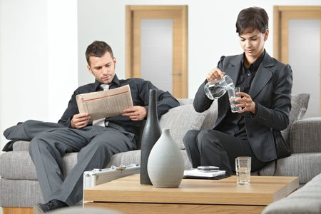 Business people sitting on sofa at office anteroom waiting. photo