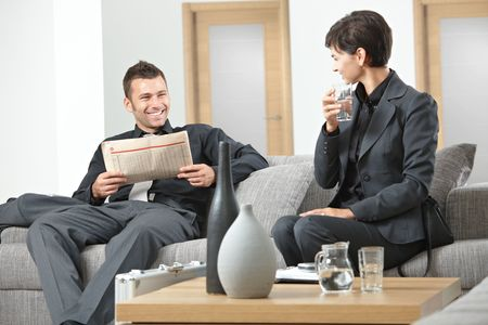 Business people sitting on sofa at office anteroom waiting and talking photo