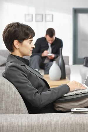 Young attractive businesswoman sitting on sofa at office lobby working with laptop computer, smiling. photo