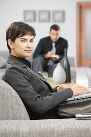 Young attractive businesswoman sitting on sofa at office lobby working with laptop computer, smiling. Stock Photo - 5766968