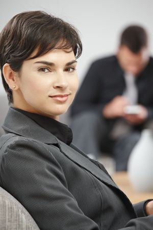 Portrait of young attractive businesswoman sitting at office lobby, smiling. photo