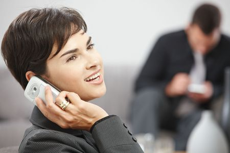 Happy young businesswoman sitting on sofa at office talking on mobile phone, smiling. photo