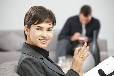 Happy young businesswoman sitting on sofe at office writing notes to personal organizer, smiling. Stock Photo - 5766971