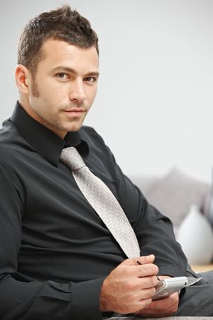 Young businessman sitting on sofa at office lobby using palmtop organizer. photo