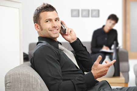 Young businessman sitting at office lobby talking on mobile phone, smiling. photo