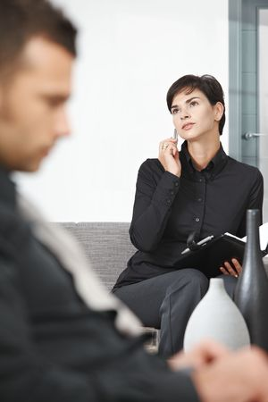 Young businesswoman sitting on sofa at office talking on mobile phone. photo