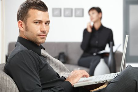 Young businessman sitting at office lobby working with laptop computer. photo