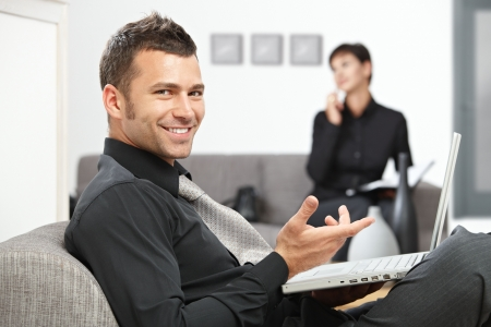 Young businessman sitting at office lobby working with laptop computer, smiling. photo