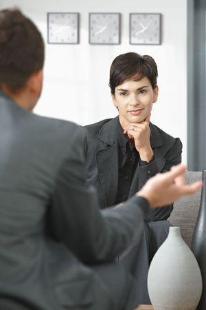 talking businessman: La empresaria joven sentado en el sof� en la oficina escuchando a hablar de negocios, sonriendo.