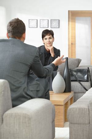 koncentrace: Young businesswoman sitting on sofa at office listening to talking businessman, smiling.