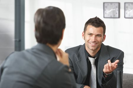 Young businessman sitting on sofa at office talking to businesswoman, smiling. photo
