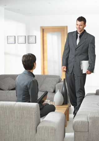 Business meeting at office lobby, young businessman arriving, smiling. Stock Photo - 5766769