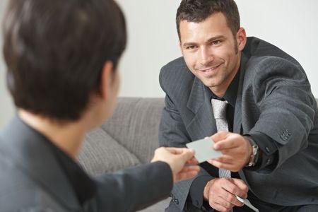 n�gocier: R�union d'affaires dans le hall de bureau, des gens assis sur le canap� de changer les cartes professionnelles.