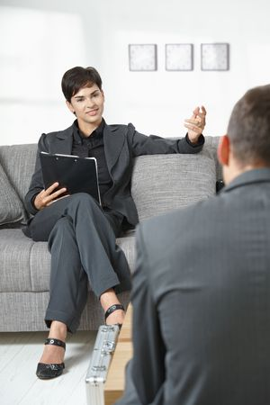 Business meeting at office. Female consultant sitting on sofa talking to partner, smiling. Stock Photo