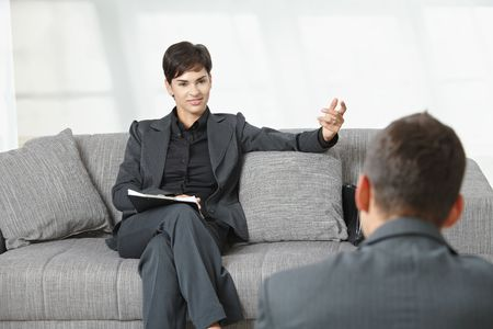 Business meeting at office. Businesswoman sitting on sofa having job interview, smiling. photo