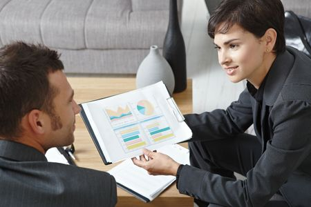 Business meeting at office. Youing businsspeople sitting on sofa, talking over financial charts. High angle view. Stock Photo - 5766781