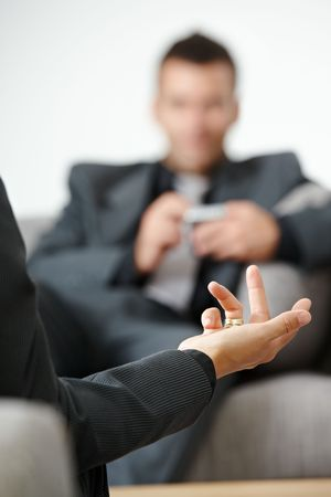 Business meeting at office. People sitting on sofa, talking. Focus on explaining female hand. photo