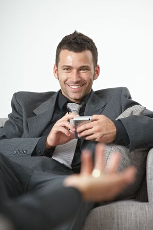 formal attire: Business meeting at office. Happy businessman sitting on sofa, talking, smiling. Stock Photo