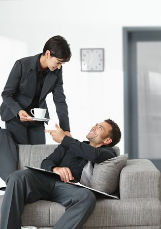 People at office. Businesswoman serving coffee to tired businessman. photo