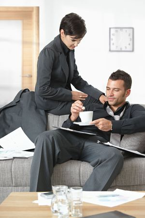 People at office. Businesswoman serving coffee to tired businessman. Stock Photo - 5766771