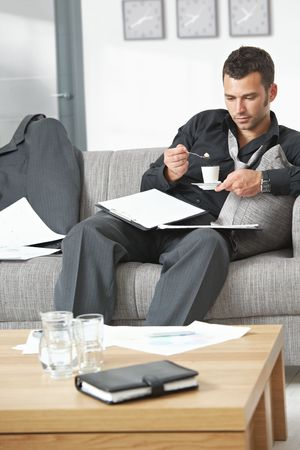 People at office. Tired businessman sitting on sofa looking at documents drinking coffee. photo